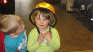 Alla fick prova hur en brandhjälm känns. Här är det Estelle som provar och Isac som undrar hur det känns.