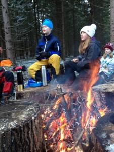 Erik och Sofie vid den varma sköna brasan lyssnar intresserat när Örjan berättar.